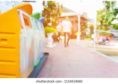 Man use mobile phone,blur image of the bins in a park as background.