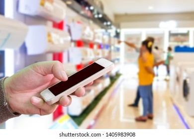 Man use mobile phone,blur image of air conditioning shop as background. Global warming in Asia causes people to buy air conditioners.