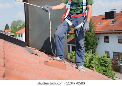 man use safety equipment - rope, gloves and harness for shingles repair work on the house roof.