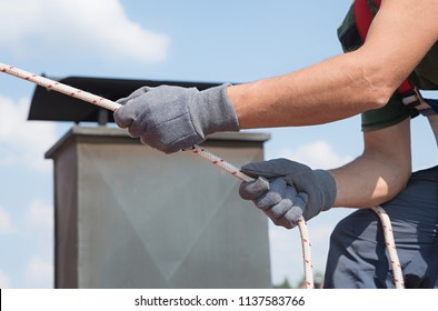 man use safety equipment - rope, gloves and harness for repair work on the house roof