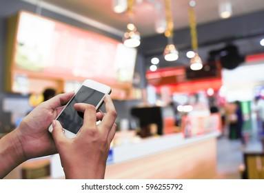 Man use smart phone, blur image of coffee shop.