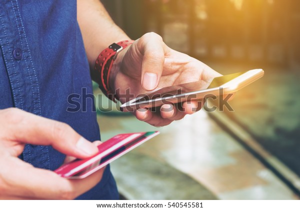 Man benutzt Smartphone und hält Kreditkarte mit Online-Shopping. Online-Zahlungskonzept.