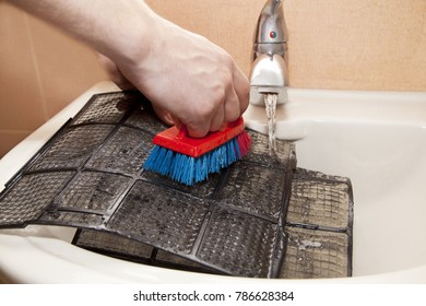 Man uses cleaning accessories and water to clean the air conditioner filter. Put in sink flush the mesh with