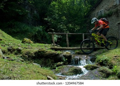 man uses an electric bicycle, e-bike, ebike, to cross a small river, splash water, summer, mountain, sports, adventure, freedom, alps, Como Lake, Italy