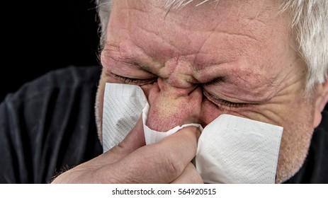 A man uses a handkerchief, he has a strong flu or allergy