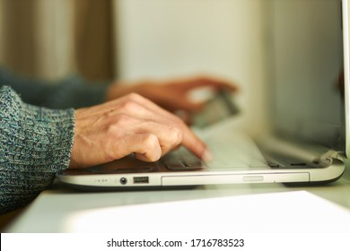 A man uses his laptop at home to shop online with his credit card. Online shopping concept. Men buy online with a credit card.