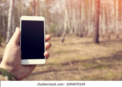 A man uses his mobile phone on the nature. Vintage toned image