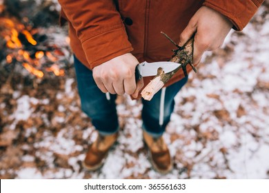 A man uses a knife to whittle a stick out hiking