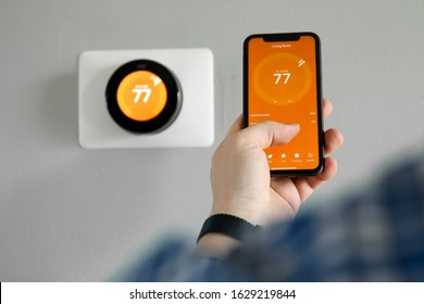 Man uses a mobile phone with smart home app in modern living room