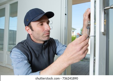 a man uses a screwdriver to adjust a glass door