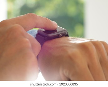 Man uses smart watch app.  Close-up hand. Sun lens flare.
