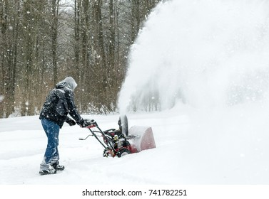 Man  uses snow blower to clear snow from driveway