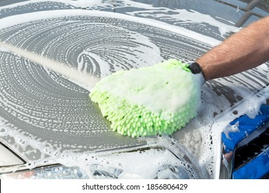 A man uses a soft, green micro fiber mitt mied with soapy water to wash his car.