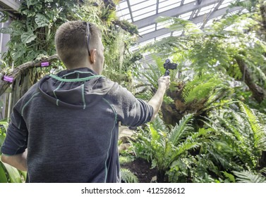 A man uses a sports camera stabilizer filming plants in a glass house