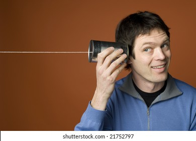 man uses tin can and string to listen to a message