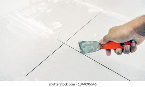 Man uses Trowel to remove old grout. Replace the old grout between the tiles. Mining tiles for rerouting.