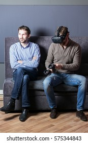 man uses virtual reality goggles and his friend sits and looks at him