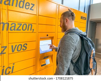 Man using Amazon Locker in shopping mall, orange pick up point for mail order goods with Amazon brand logo on it. Mobile photography. Lyon, France - February 23, 2020