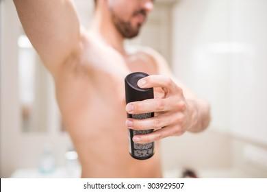 Man using antiperspirant in bathroom