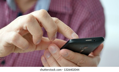 A man using apps on a mobile touchscreen smartphone. Concept of modern technology, shopping online and smart phones