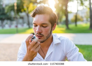 Man using an asthma inhaler. Man about to use asthma inhaler. Close-up Of Beard Man Using Asthma Inhaler For Being Healthy. Man using a pressurized cartridge inhaler extended pharynx, Bronchodilator