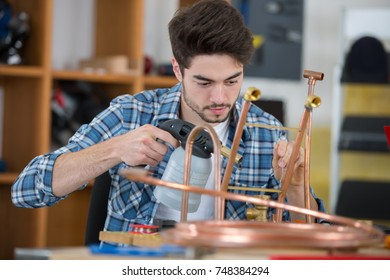 man using blowtorch on copper pipes