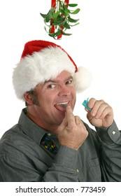 A man using a breath freshener, preparing for a kiss under the mistletoe.