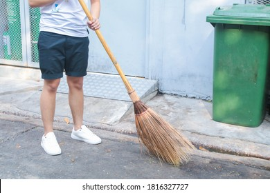 Man using broom sweep the street or floor garbage cleaning service concept city.Maintenance worker in park garden cleans the roads with broom .Copy space