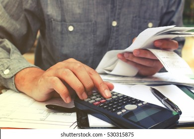 Man using calculator and calculating bills in home office.