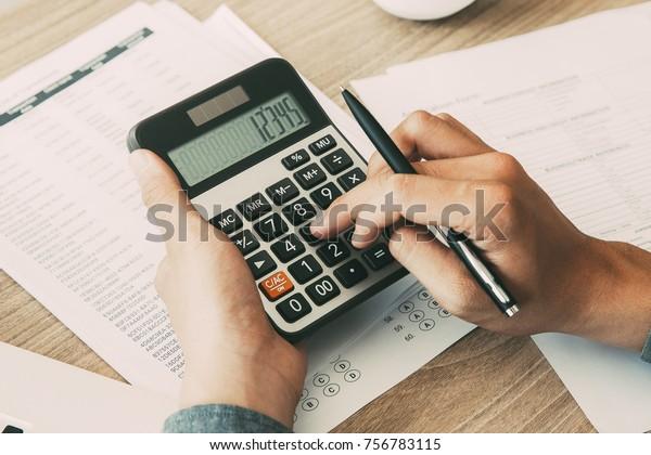 Mann, der mit dem Rechner Einkommen und Ergebnis berechnet