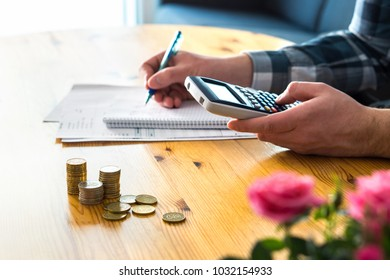 Man using calculator and counting budget, expenses and savings. Low income family living cost and rising prices concept. Calculating and budgeting. Making retirement plan. Writing notes on paper.