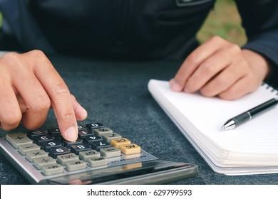 Man Using calculator on table.