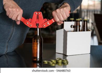 Man using capper to put metal caps on beer bottle