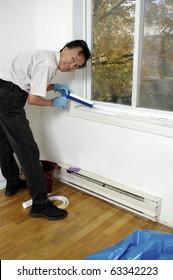 man using caulk-gun caulking  window sill to winterize insulate home