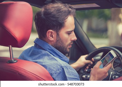 Man using cell phone texting while driving. Risky, reckless driver concept