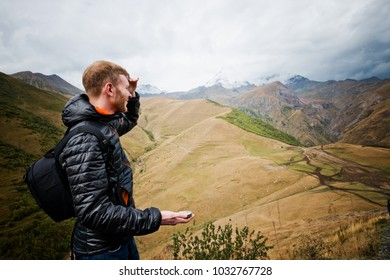 man using a compass in the mountains