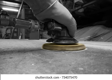 Man using compressed air orbital sander with selective color