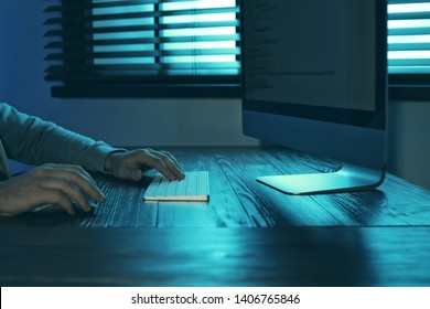 Man using computer in dark room, closeup. Criminal offence