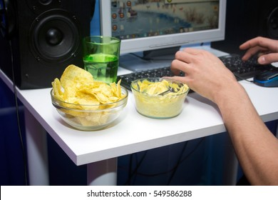 Man using a computer and eating fastfood. Concept of sedentary lifestyle and unhealthy eating habits