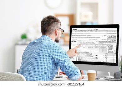 Man using computer for filling in individual income tax return form at table