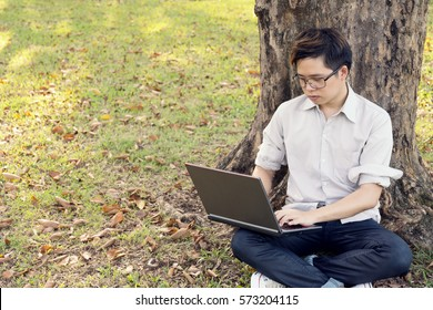 man is using computer laptop for working at outdoor in public park.