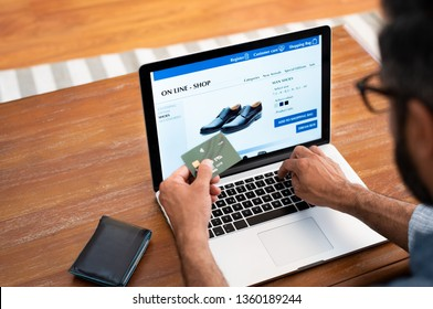 Man using credit card to do shopping online with laptop. Mature man buying formal shoes online. Man making online payment with credit card and laptop.