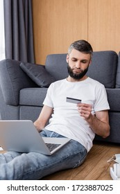 Man using credit card and laptop near medical mask and headphones on floor in living room