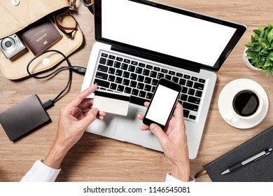Man using credit card with mobile phone and laptop and coffee cup on office desk.Online payment Concept.