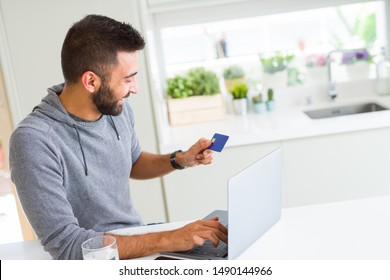 Man using credit card as payment metod when shopping online using laptop, blank screen concept