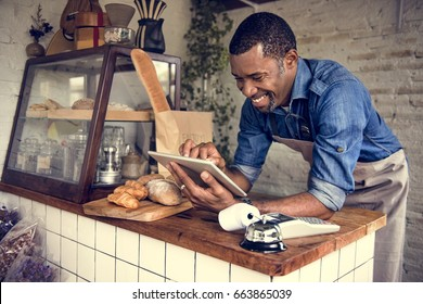 Man using devices for online business order at bakehouse