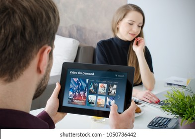 Man using digital tablet for watching movie on VOD service. Video On Demand television internet stream multimedia concept