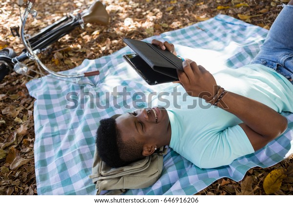 Man using digital while lying on a picnic blanket in the park
