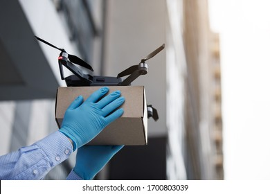 Man using drone for fast delivery of package with products, safety delivery on quarantine, copy space