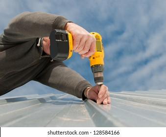 Man using  an electric drill to fasten down a metal roof, view from below, up against partly cloudy sky